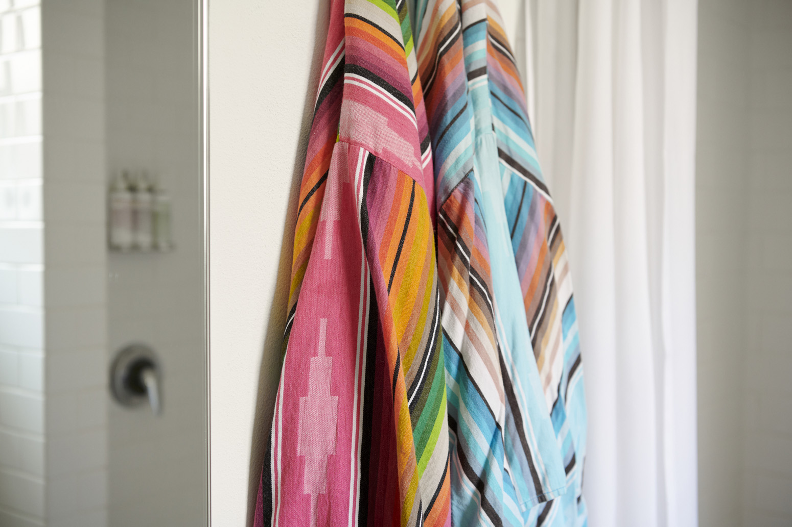 A set of colorful bathrobes hanging on a wall