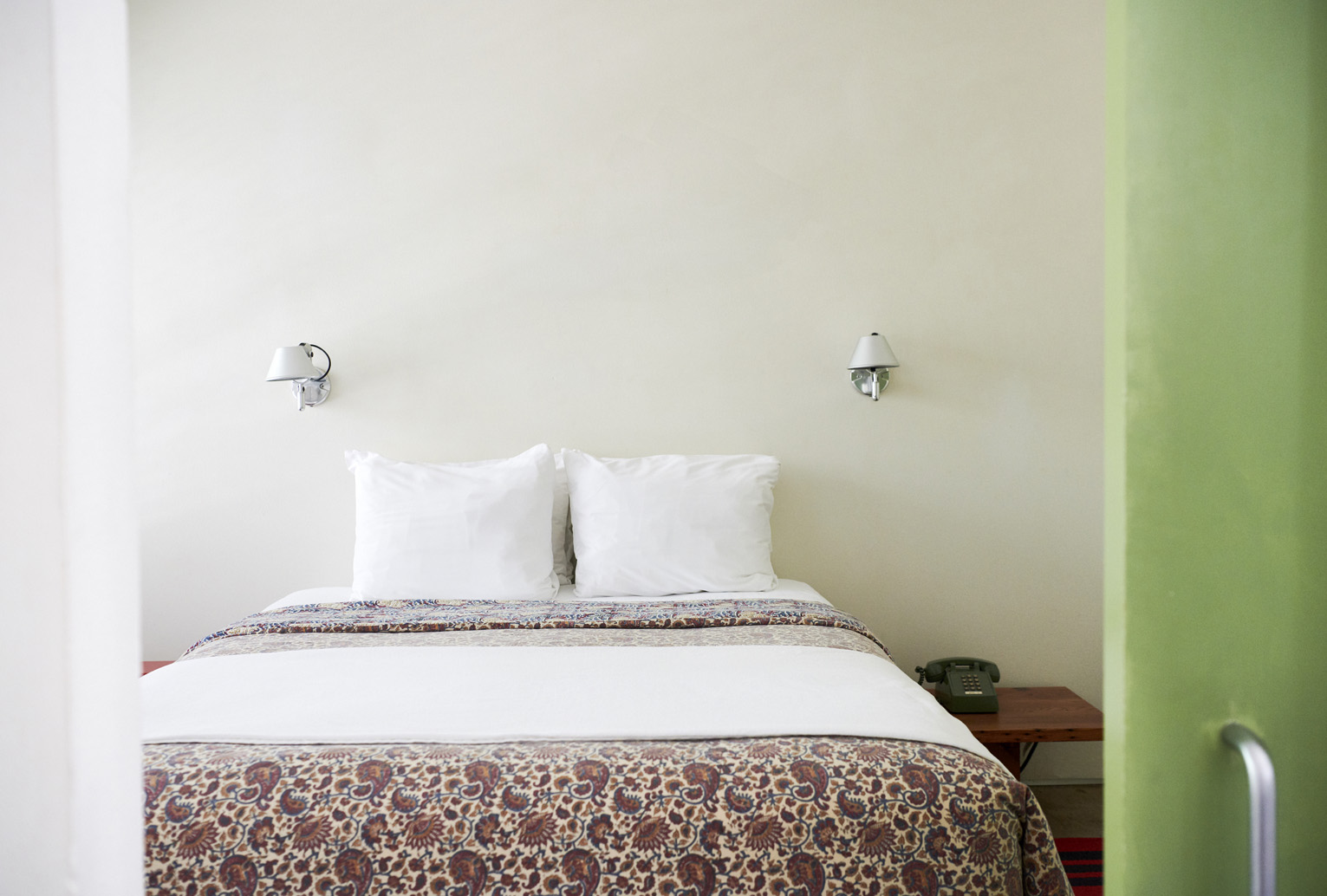 A large bed with patterned sheets next to a bright green door
