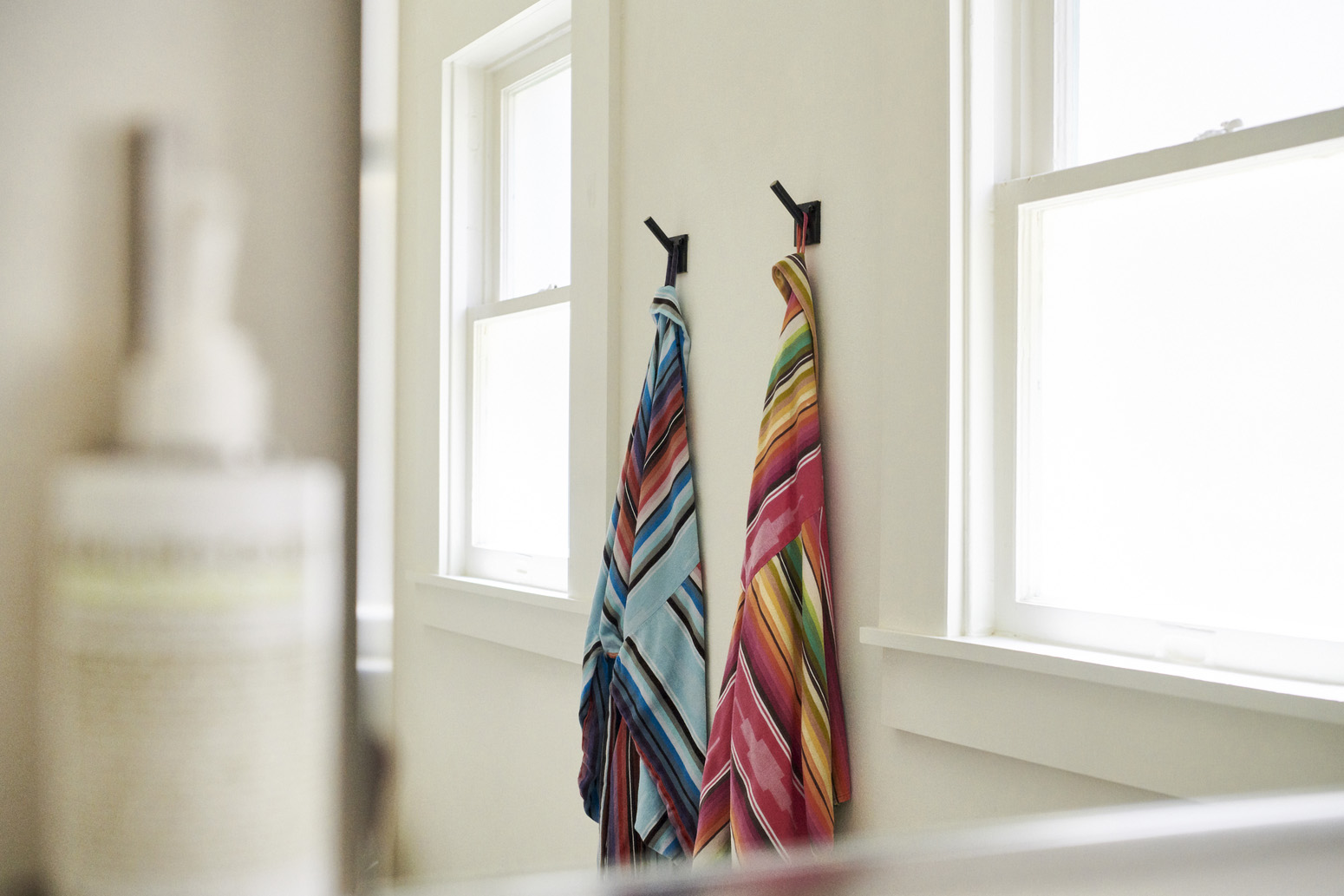 A set of patterned bathrobes hanging on a wall between two bright windows