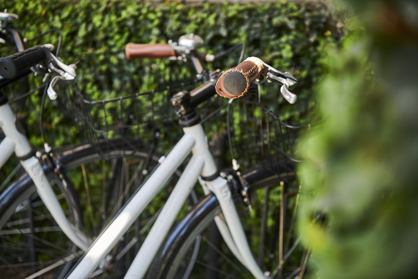 A white bike with brown leather handles next to some shrubbery