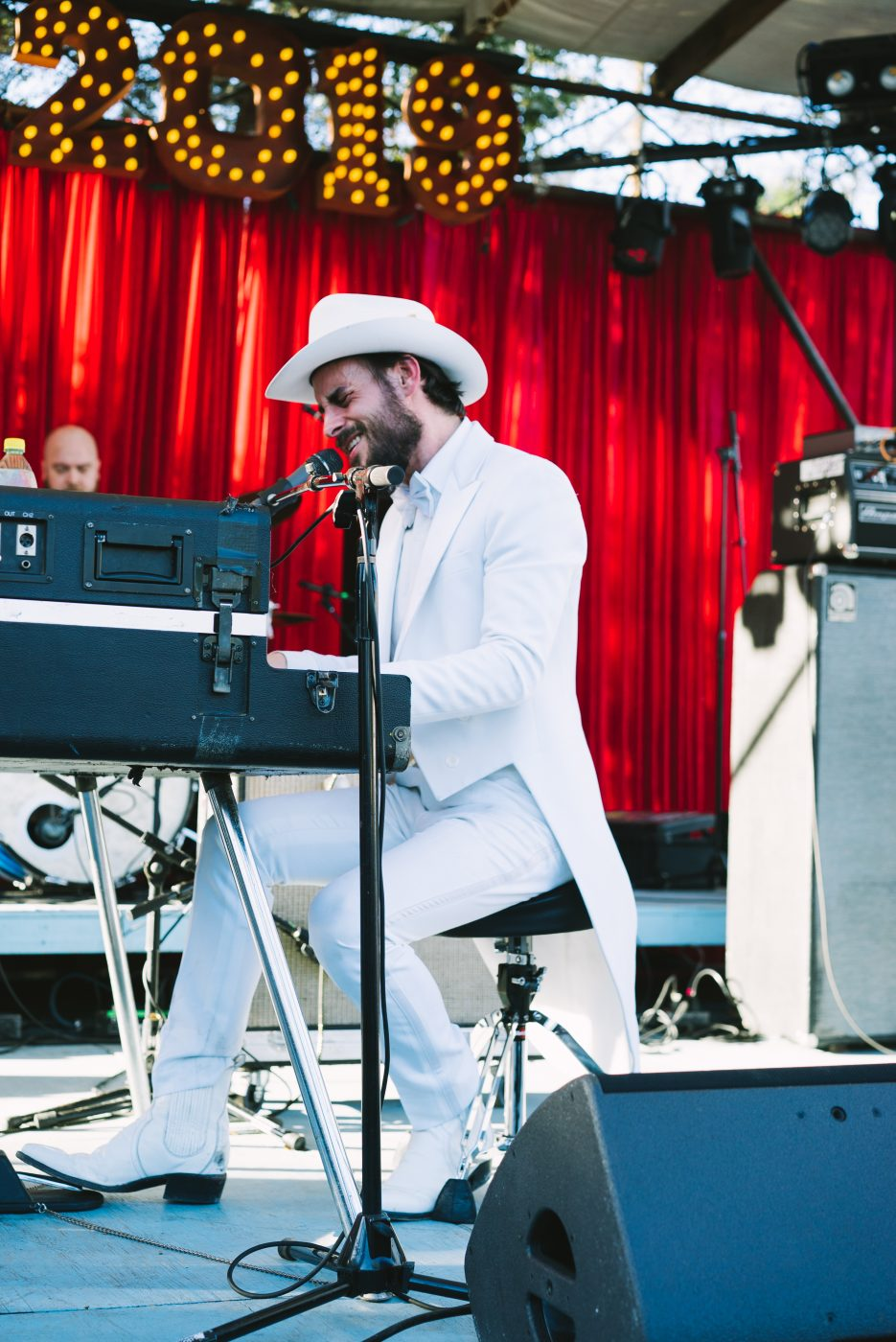 Musician performing on staging wearing a white suite and white cowboy hat